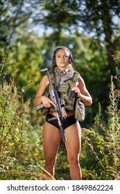 young caucasian athletic female in short top and shorts holding gun posing in forest alone, slim female in military wear ready to shoot, hunt