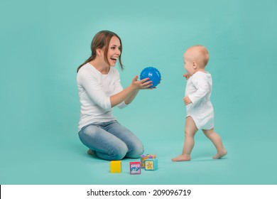 Young Caucasian attractive smiling mother playing with her cute little son with a ball and colored blocks, baby boy wearing bodysuit running isolated on blue