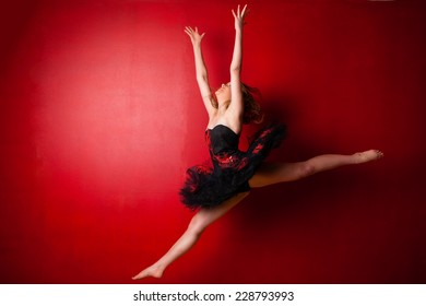 Young Caucasian ballerina executing a jump against bright red wall, throwing her hands in the air