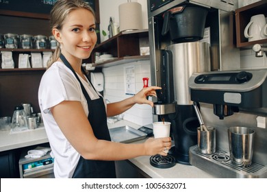 Young Caucasian barista hands holding paper cup making coffee using coffee machine. Woman pouring coffee from professional espresso machine. Small business and person at work concept