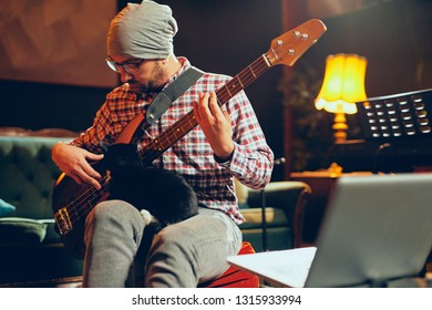Young Caucasian bass guitarist plauing his instrument and holding cute little cat in lap while sitting in home studio.
