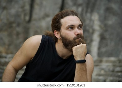 Young caucasian bearded man with curly hair sitting on a rock with reflexive expression on his face. He's wearing an activity band and some piercings on his ear.