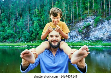 Young caucasian bearded man is holding his son on his shoulders, both are smiling and laughing, father and son are playing in  forest near river, eco-tourism.