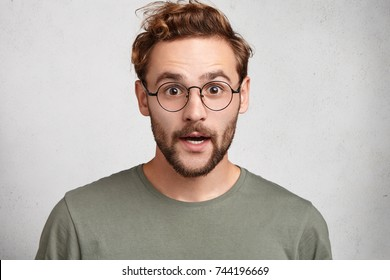 Young Caucasian bearded man looks in surprisment, opens mouth, surprised expression, isolated over white background. Shocked male student has deadline to prepare for exams. Emotional person.