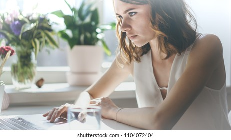 Young caucasian beautiful woman working on a laptop sitting at the table in living room of modern house.Closeup.