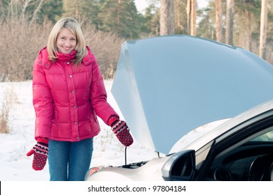 Young caucasian blond woman standing by her broken car on a winter road