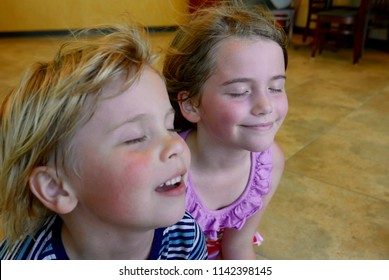 Young Caucasian blonde boy and girl cooling off in front of a fan with their hair blowing in the air