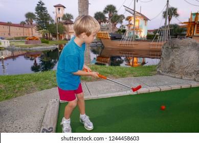 Young, Caucasian, blonde boy playing miniature golf