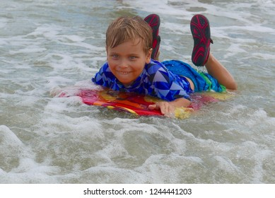 Young Caucasian blonde boy smiling and riding a colorful boogie board in shallow ocean waves