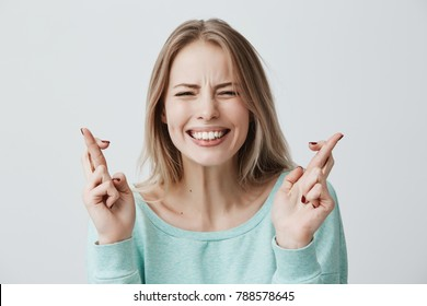 Young caucasian blonde female closing her eyes crossing fingers with hope, anticipating important news. Beautiful girl with hopeful expression gesturing with fingers, showing white teeth