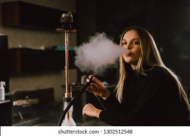 Young caucasian blonde girl smoking hookah at luxury interior with custom v8  car engine table. Leather sofa and beautiful smile