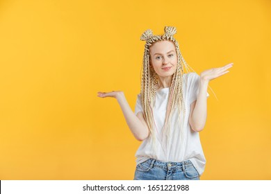 Young caucasian blonde woman gestures and shows with hands an apology for inconvenience. Portrait isolated on yellow with copespace