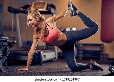 Young Caucasian blonde woman with ponytail and in sportswear doing exercises on the gym floor.