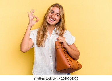 Young caucasian blonde woman wearing a leather bag isolated on yellow background  cheerful and confident showing ok gesture.