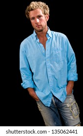 A young, Caucasian, blue eyed, blonde haired male. He is wearing a blue button up shirt, blue jeans and has his hands in his pockets.