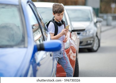Young caucasian boy is busy with his mobile smart phone not paying attention to the danger of traffic in the street
