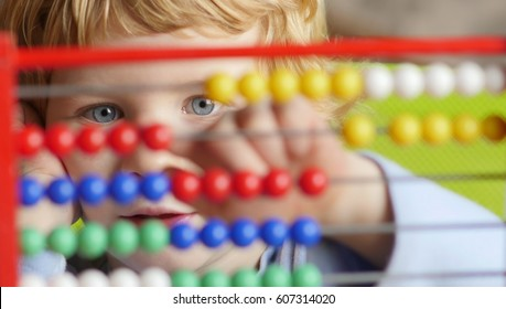 Young caucasian boy early learning counting on abacus.