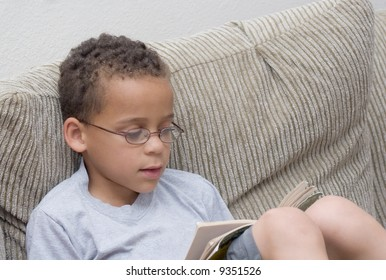 Young Caucasian boy with glasses reading a paperback book while relaxing on the couch