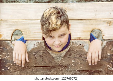 Young caucasian boy in medieval pillory. Misery theme. Punishment device. Yellow photo filter.