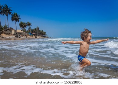 Young caucasian boy running happy into the ocean. From a tropical beach with old cottages and palm trees at Sankofa beach Ghana, near Accra City, Western Africa.