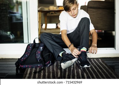 Young caucasian boy sitting on the house entrance tying sneaker ropes