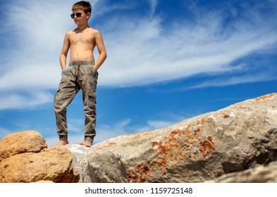 Young caucasian boy, wearing camo pants and sun glasses, standing on rocks near a beach in Bibione, on the Adriatic Sea, Italy