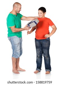 Young caucasian boy wearing an orange t-shirt and blue jeans is getting a gift from his father. The dad is wearing a green shirt.