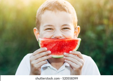 Young caucasian boy a white shirt smiles with his watermelon. Summer, field, nice sunshine, sunset