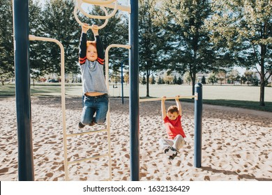 Young Caucasian boys friends hanging on monkey bars and pull-up bars in park on playground. Summer outdoor activity for kids. Active children doing exercises sport. Healthy happy childhood.