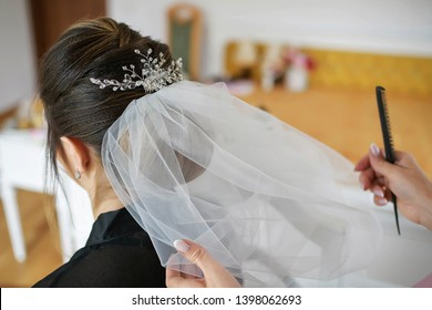 Young Caucasian bride getting her hair done for her wedding day. Hair stylist working on a woman's dark hair, setting a tulle veil in a sophisticated coiffure using bobby pins and a fine-toothed comb