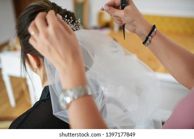 Young Caucasian bride having her hair done for her wedding day. Hair stylist working on a woman's dark hair, setting a tulle veil in a sophisticated coiffure using bobby pins and a fine-toothed comb
