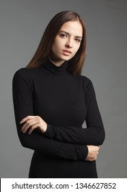 young caucasian brownhair woman in black turtleneck isolated on gray background