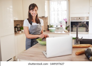 Young Caucasian brunette in apron grating carrots in bowl, preparing dinner and looking at lapotp while standing in kitchen