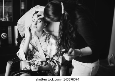 young caucasian brunette bride having make up in the morning