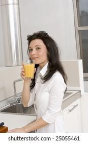 young caucasian brunette drinking orange juice in her kitchen dressing casual wear