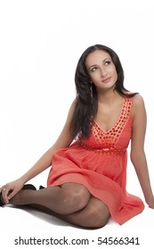 young caucasian brunette girl in peachy dress making curious look sitting isolated over white background