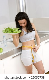young caucasian brunette in kitchen with a sald dish and a centimeter to measure her hips.Concept of correct food to have a slim body