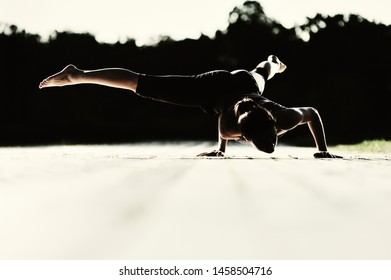 Young caucasian brunette woman doing yoga in the park at night. View of yoga asana silhouette.