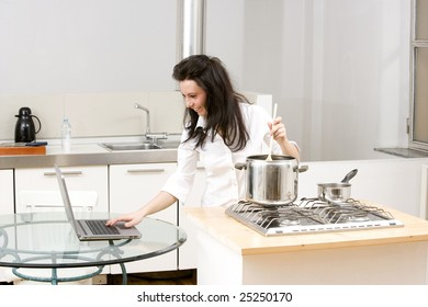 young caucasian brunette working with laptop while cooking in her kitchen.Concept of on line receipt,hard working.
