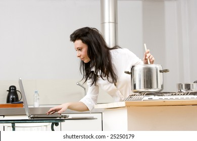 young caucasian brunette working with laptop while cooking in her kitchen.Concept of online receipt,hard working.