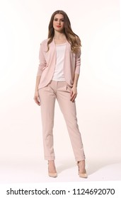 young caucasian business woman executive posing in designer formal summer pink powder pant suit high heels stiletto shoes full body length isolated on white