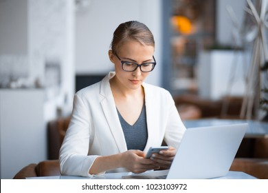 young caucasian business woman in glasses behind a laptop with a phone in hands