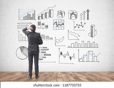 Young caucasian businessman with black hair wearing a dark suit and scratching his head looking at graphs and data on concrete wall. Business planning and information concept