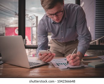 Young Caucasian businessman in denim shirt is standing in office at table and is using laptop with charts, graphs and diagrams on screen. On table is smartphone and charts. Man working.