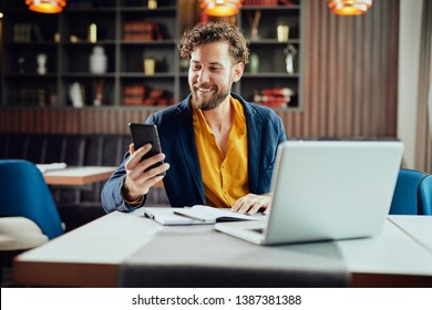 Young Caucasian businessman dressed smart casual using smart phone while sitting in cafe. On the desk laptop.