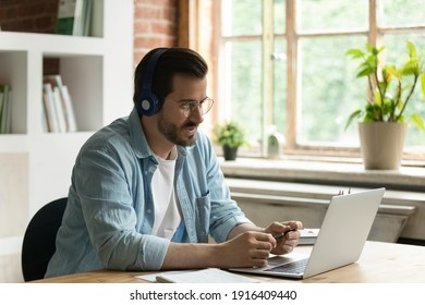 Young Caucasian businessman in earphones work on computer online talk speak on video call with client. Male employee in headphones use laptop have webcam digital conference with customer.