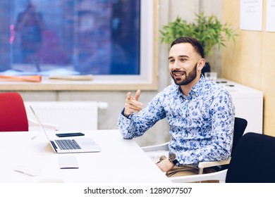 Young caucasian businessman gesturing during discussion in his office. Man working in office
