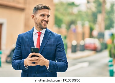Young caucasian businessman smiling happy using smartphone at the city.