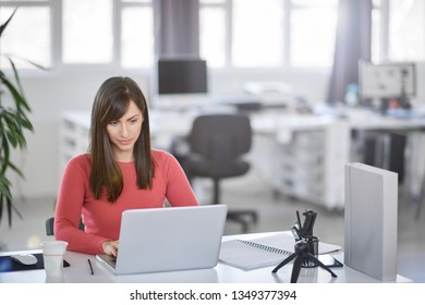 Young Caucasian businesswoman sitting in modern office and using laptop.
