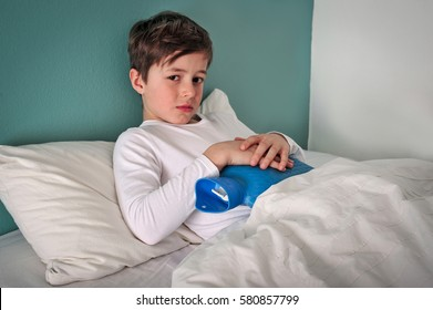 Young caucasian child is in bed sick with a cold holding a hot water bottle to his belly